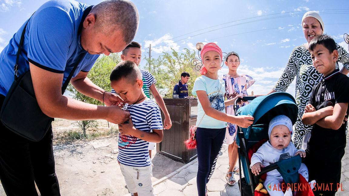 Ojciec zawiesza znak rodowy na szyi swojego syna w Arstanbaba